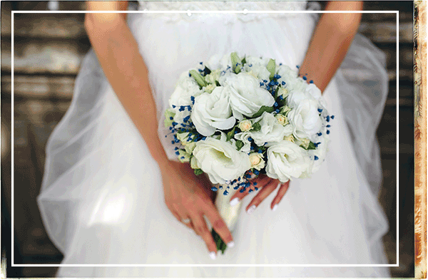 A bride holds a bouquet of white flowers before her
