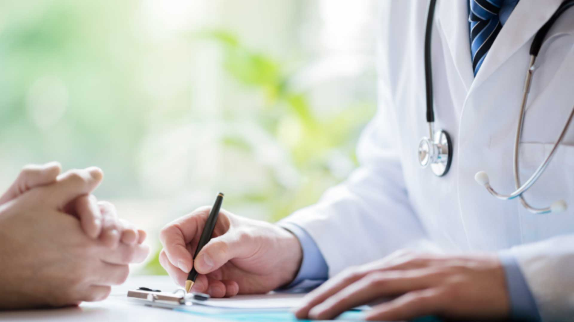 Cosmetic Procedures Doctor taking notes while consulting with patient
